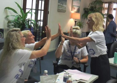 Rose Nierman high-fiving Attendees at a Medical Billing/ CrossCoding CE Course