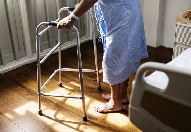patient leaning on a walker wearing a hospital gown in a hospital room
