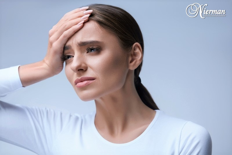Woman holding head in pain due to TMJ