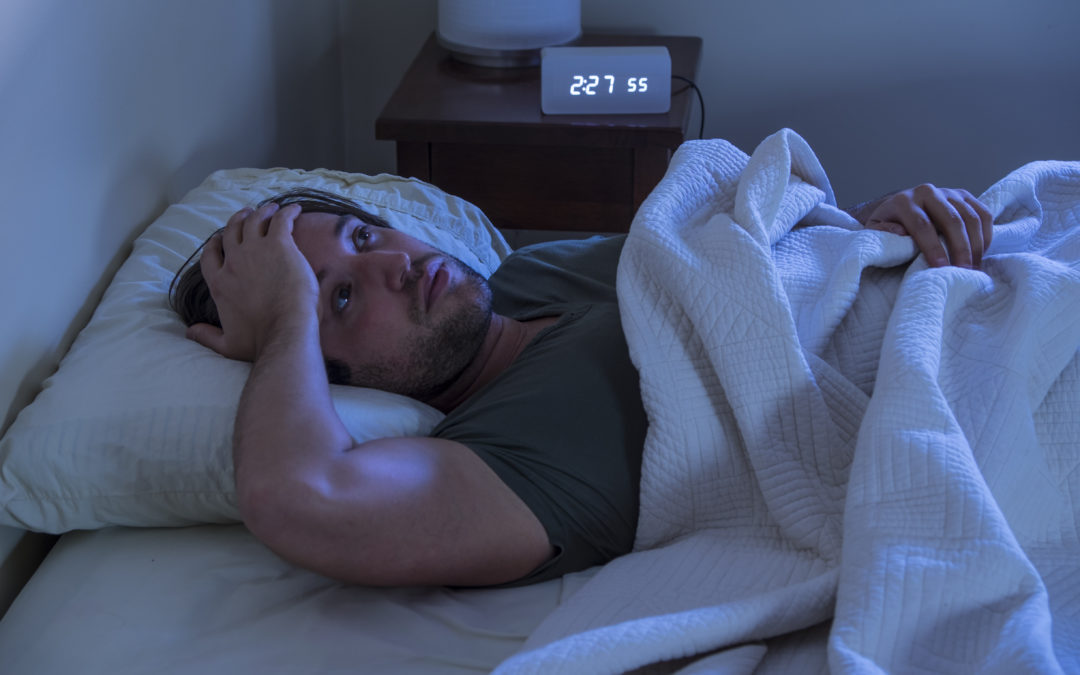 man lying awake holding his head due to a headache because of sleep deprivation